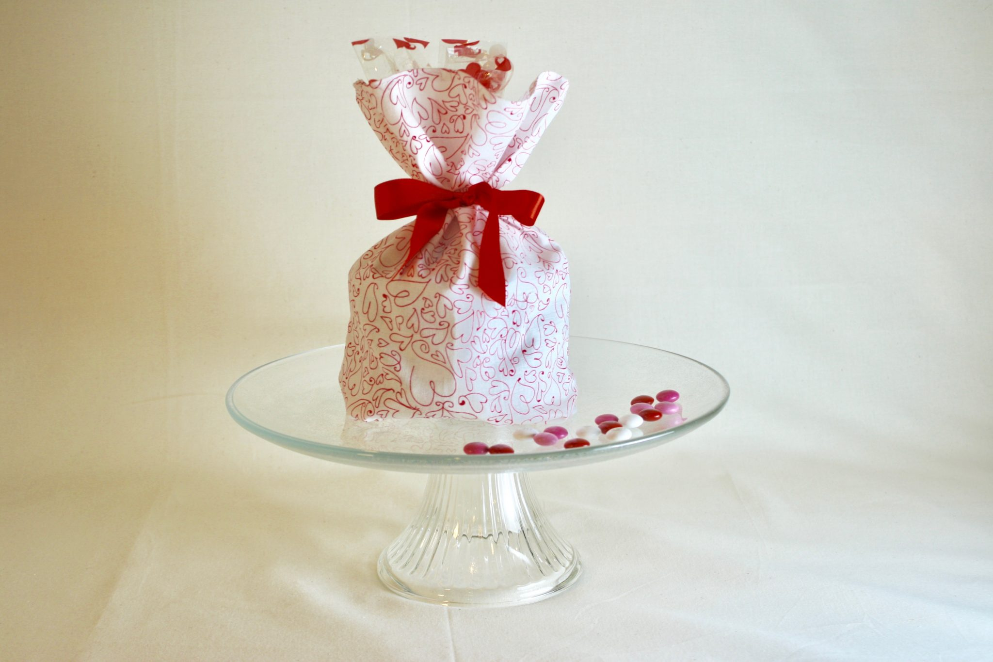 Picture of our Sampler Stack wrapped in a Valentine cloth wrap and tied with a red ribbon.
