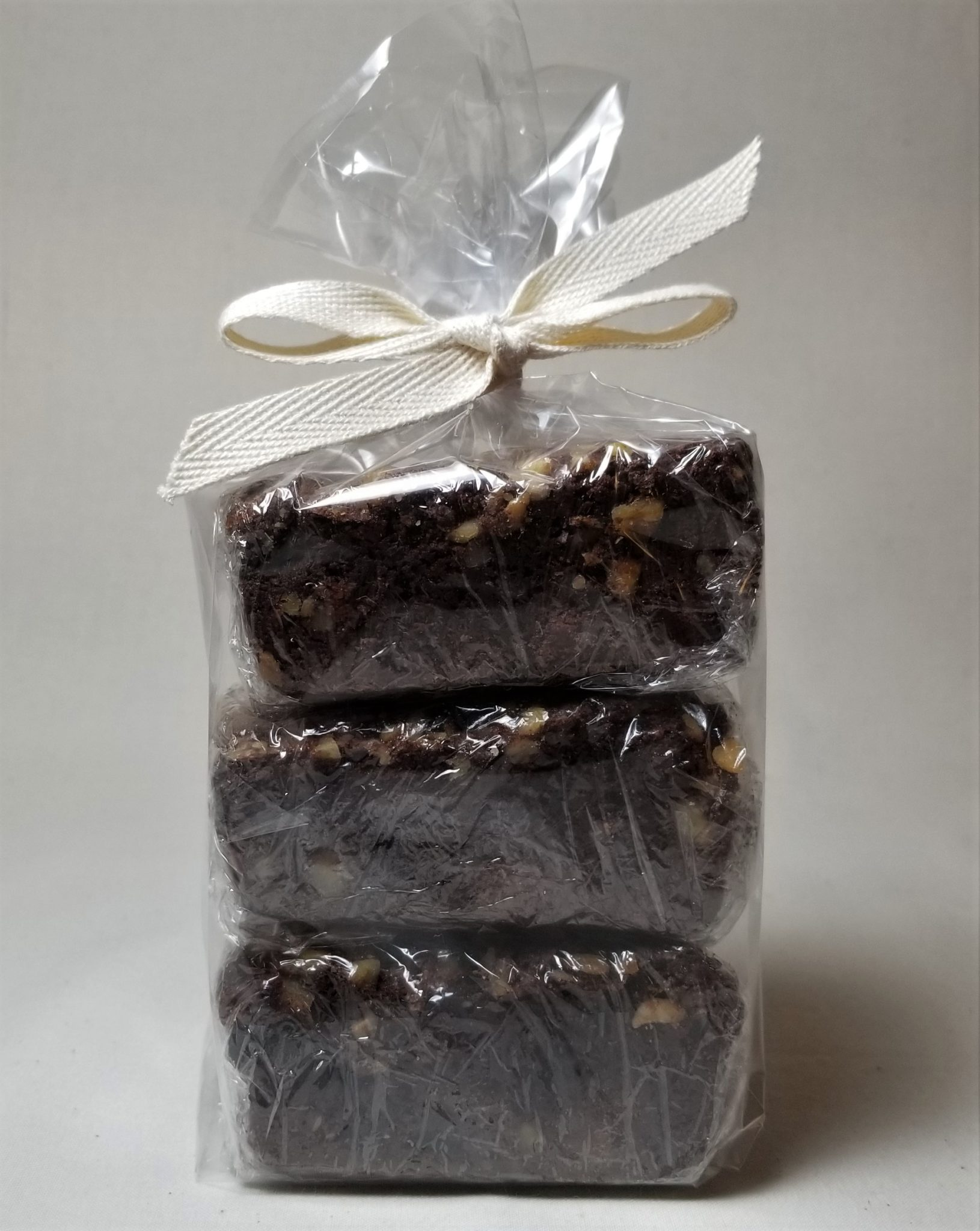 Stack of three individually wrapped brownies inside a cello sleeve and tied with a cotton ribbon.