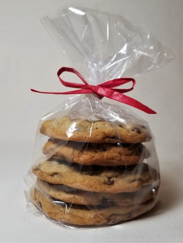 Stack of five chocolate chip cookies, individually wrapped inside a cello sleeve and tied with a red raffia ribbon.