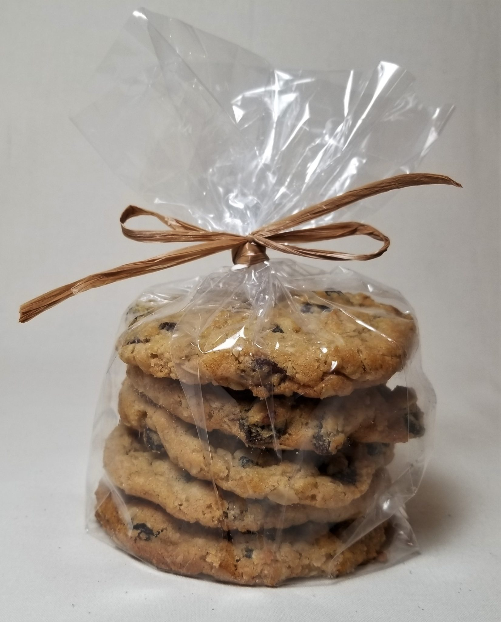 Stack of five Oatmeal Raisin Cookies, individually wrapped inside a cello sleeve and tied with a brown raffia ribbon.