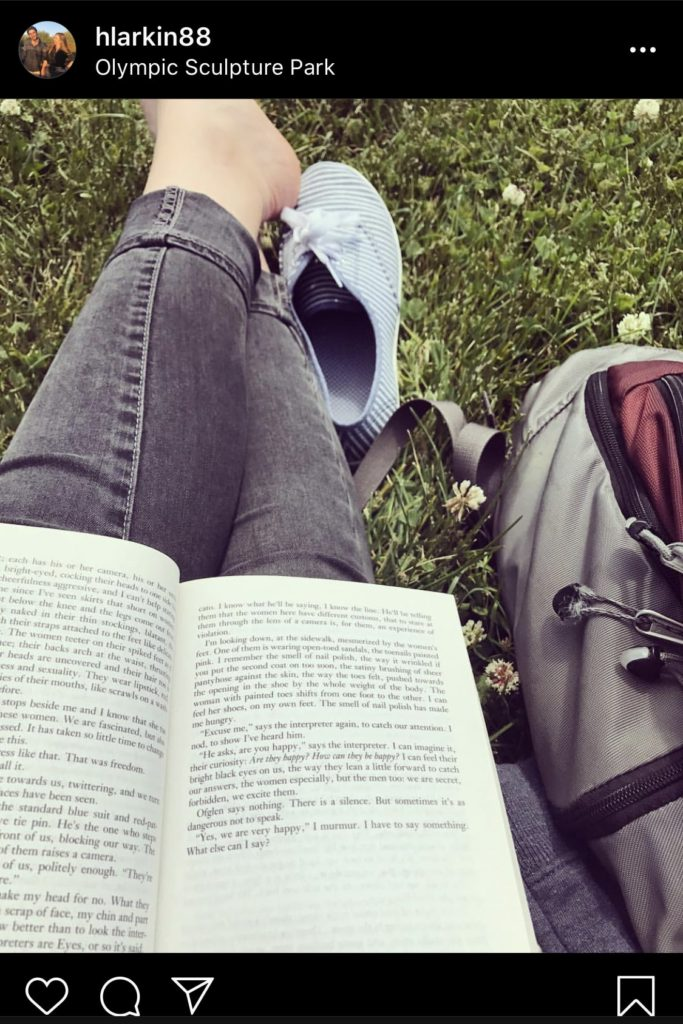 An  open book in my lap sitting on a grassy field with my shoes off.