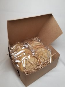 A dozen Classic Oatmeal Raisin Cookies , each individually wrapped and packaged in a kraft bakery box.
