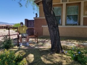 Picture of Dad sitting on bench on the flagstone walkway