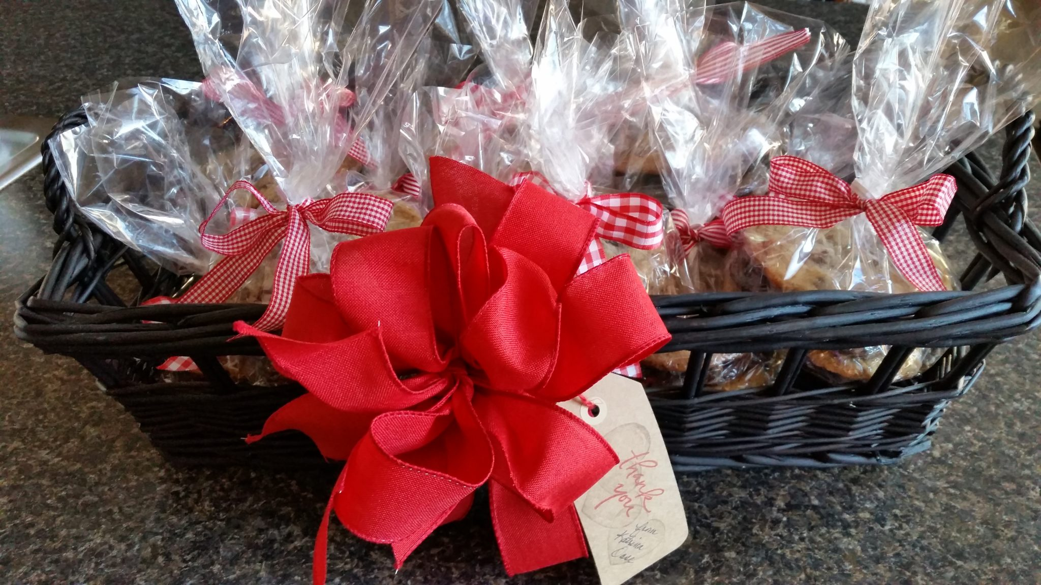 Picture of a gift basket of stacks of cookies all wrapped and tied with a gingham bow.